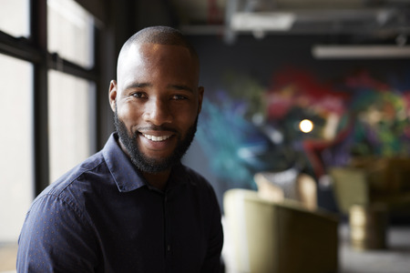 Mid adult black male creative in an office social area turning to camera smiling, close up