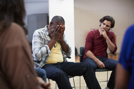 Unhappy Man Attending Self Help Therapy Group Meeting In Community Center