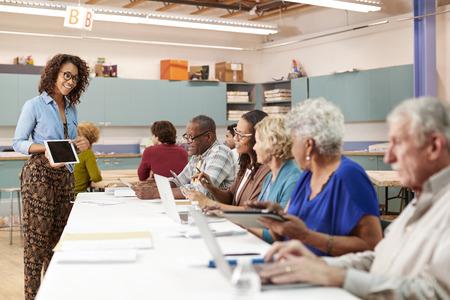 Group Of Retired Seniors Attending IT Class In Community Centre With Teacher 版權商用圖片