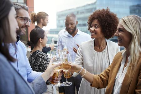 Socializar a los compañeros de oficina levantando vasos y haciendo un brindis con bebidas después del trabajo