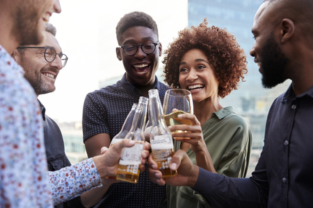 Happy creative business colleagues having a drink after work raise glasses to make a toast Stock Photo