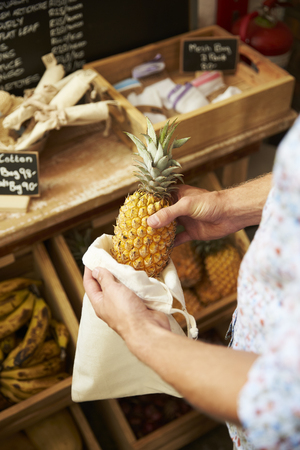 Close Up Of Man Putting Pineapple Into Reusable Cotton Bag In Plastic Free Grocery Store Banco de Imagens