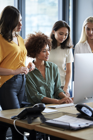 Four female creatives working around a computer monitor in an office, side view, vertical, close up