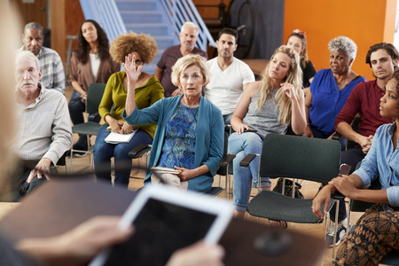 Mujer haciendo preguntas en la reunión de barrio del grupo en el centro comunitario Foto de archivo