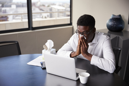 Young black businessman sitting at an office desk blowing his nose into a tissue, elevated view