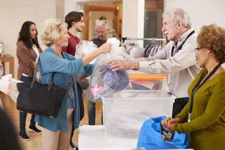 People Donating Clothing To Charity Collection In Community Center Imagens
