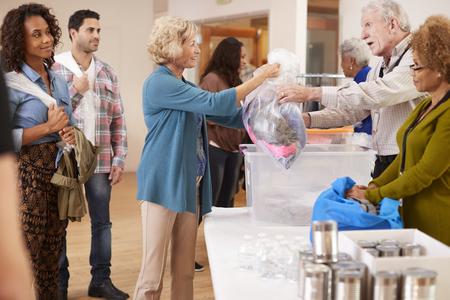 Personnes faisant don de vêtements à la collecte de charité dans le centre communautaire
