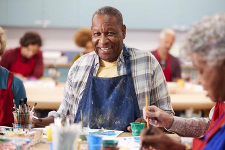 Portret van een gepensioneerde oudere man die een kunstles bijwoont in het gemeenschapscentrum Stockfoto