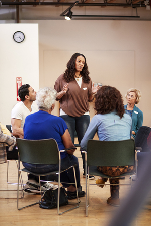 Woman Standing To Address Self Help Therapy Group Meeting In Community Center Imagens