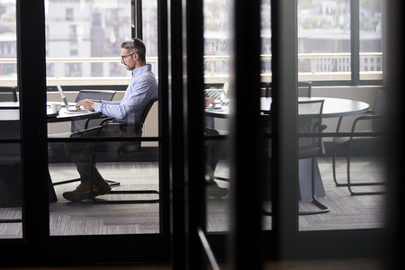 Middle aged white businessman working alone in a meeting room, seen through glass door