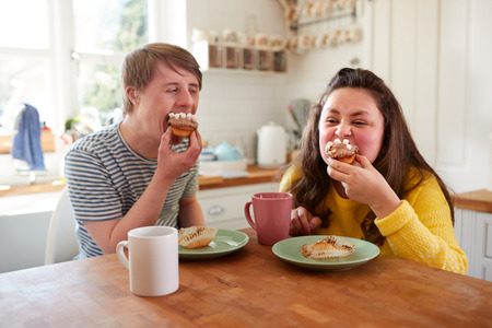 Young Downs Syndrome Couple Enjoying Tea And Cake In Kitchen At Home Foto de archivo - 122714361