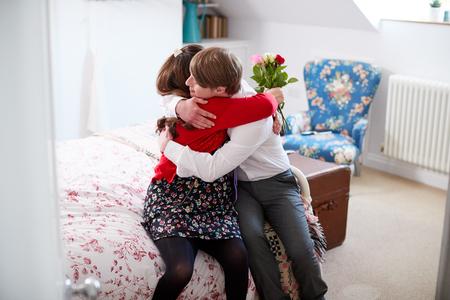 Liefdevol Young Downs Syndroom koppel zittend op bed met man die vrouw bloemen geeft