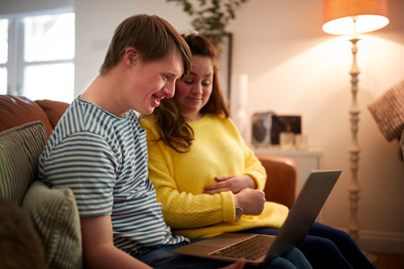 Young Downs Syndrome Couple Sitting On Sofa Using Laptop At Home Stockfoto