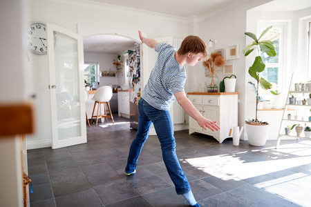 Young Downs Syndrome Man Having Fun Dancing At Home