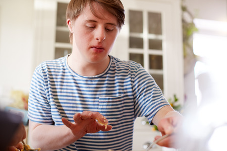 Young Downs Syndrome Man Baking Cupcakes In Kitchen At Home