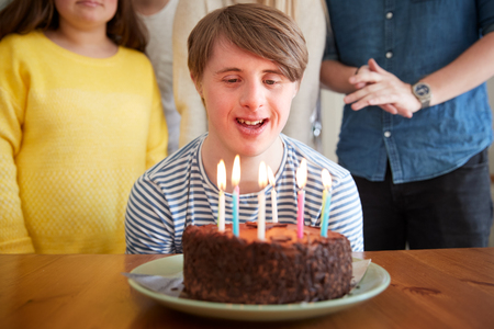 Young Downs Syndrome Man Celebrating Birthday At Home With Cake