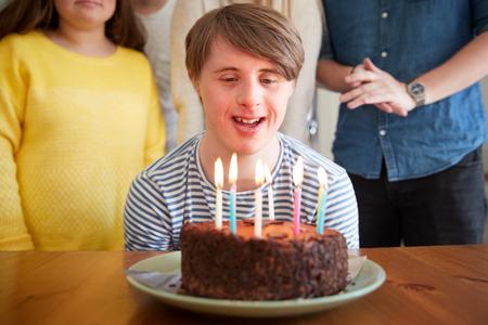 Young Downs Syndroom Man viert verjaardag thuis met taart Stockfoto