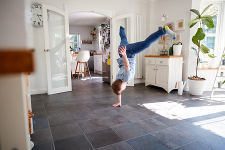 Young Downs Syndrome Man Having Fun Breakdancing At Home