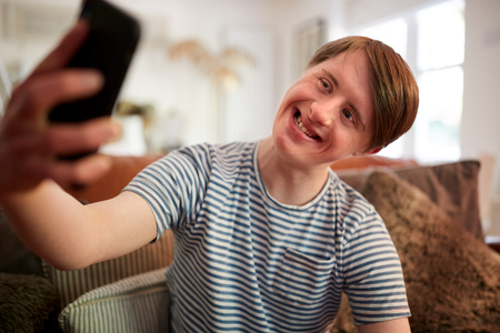 Young Downs Syndrome Man Sitting On Sofa Using Mobile Phone To Take Selfie At Home