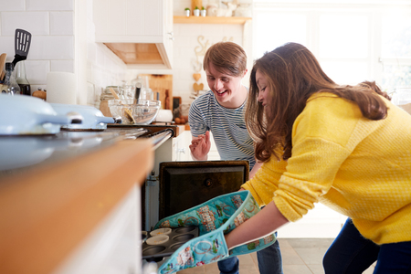 Young Downs Syndrome Couple Putting Homemade Cupcakes Into Oven In Kitchen At Home