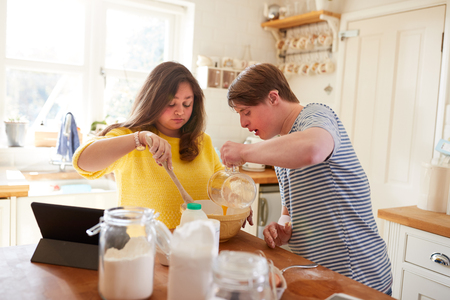 Young Downs Syndrome Couple Following Recipe On Digital Tablet To Bake Cake In Kitchen At Home Stock Photo