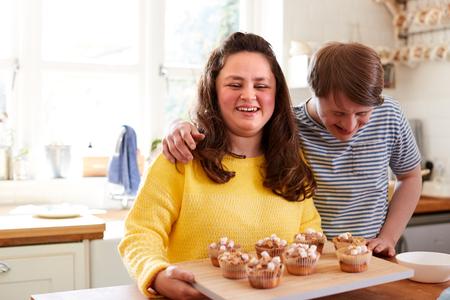 Portrait de couple trisomique décoration de petits gâteaux faits maison avec des guimauves dans la cuisine à la maison