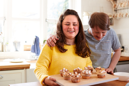 Portrait Of Downs Syndrome Couple Decorating Homemade Cupcakes With Marshmallows In Kitchen At Home