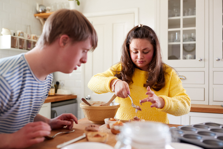 Young Downs Syndrome Couple Decorating Homemade Cupcakes With Icing In Kitchen At Home Foto de archivo - 122714406