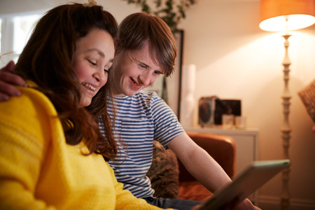 Young Downs Syndrome Couple Sitting On Sofa Using Digital Tablet At Home