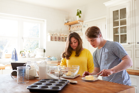 Young Downs Syndrome Couple Following Recipe On Digital Tablet To Bake Cake In Kitchen At Home Foto de archivo - 122714409