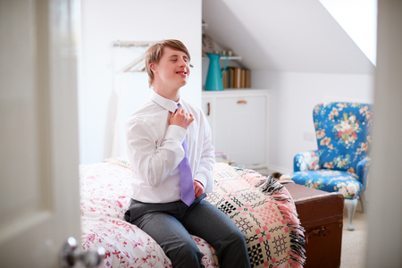 Young Downs Syndrome Man Sitting On Bed Getting Dressed For Work Stock Photo