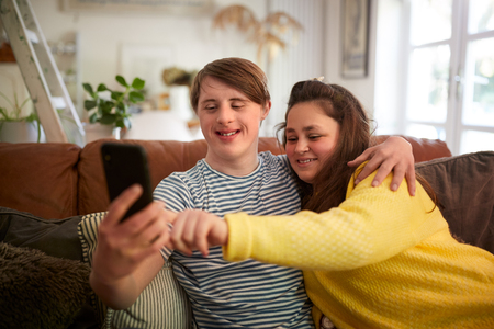Young Downs Syndrome Couple Sitting On Sofa Using Mobile Phone To Take Selfie At Home Stock Photo