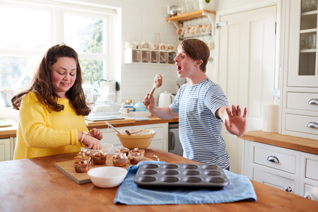 Young Downs Syndrome Couple Decorating Homemade Cupcakes With Marshmallows In Kitchen At Home 写真素材