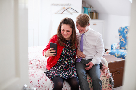 Loving Young Downs Syndrome Couple Sitting On Bed Using Mobile Phone To Take Selfie At Home