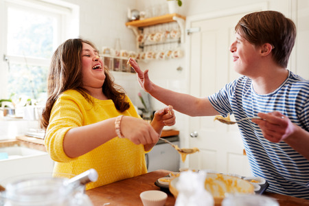 Young Downs Syndrome Couple Having Fun Baking Cupcakes In Kitchen At Home Foto de archivo - 122714472
