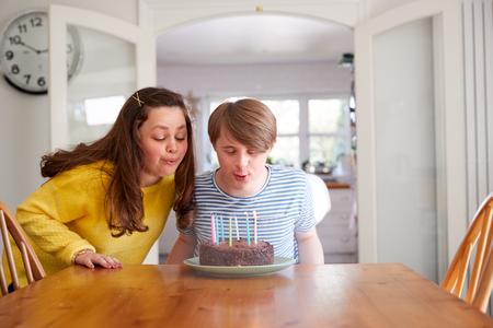 Young Downs Syndrome-paar dat verjaardag thuis viert met cake Stockfoto