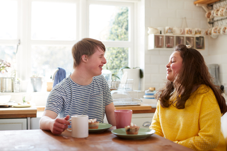 Young Downs Syndrome Couple Enjoying Tea And Cake In Kitchen At Home Stock Photo