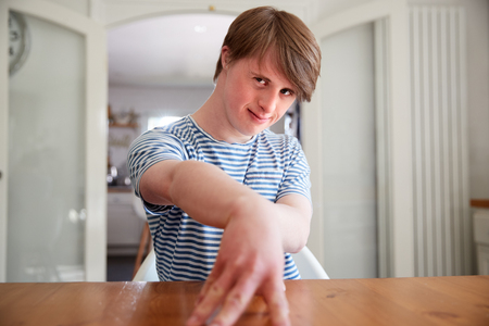 Portrait Of Young Downs Syndrome Man Sitting At Table In Kitchen Stock Photo