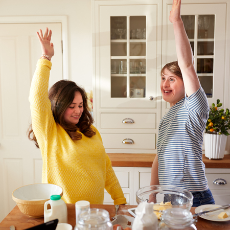 Young Downs Syndrome Couple Having Fun Baking In Kitchen At Home Stock Photo