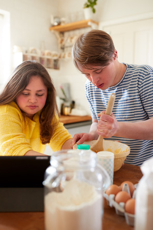 Young Downs Syndrome Couple Following Recipe On Digital Tablet To Bake Cake In Kitchen At Home Foto de archivo - 122714488