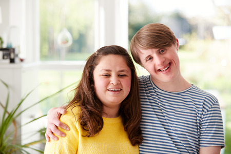 Portrait Of Loving Young Downs Syndrome Couple At Home Together