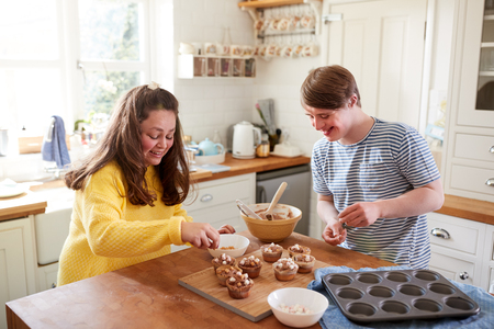 Young Downs Syndrome Couple Decorating Homemade Cupcakes With Marshmallows In Kitchen At Home Stock Photo