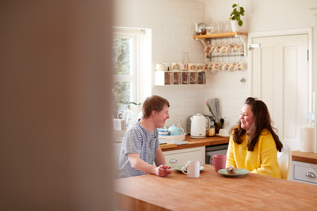 Young Downs Syndrome Couple Enjoying Tea And Cake In Kitchen At Home Foto de archivo - 122744592