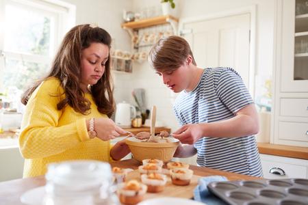 Jonge Downs Syndroom Paar Zelfgemaakte Cupcakes Versieren Met Suikerglazuur In De Keuken Thuis