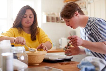 Young Downs Syndroom koppel cupcakes bakken in de keuken thuis Stockfoto