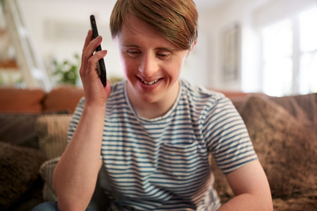 Young Downs Syndrome Man Sitting On Sofa Using Mobile Phone At Home Stock Photo