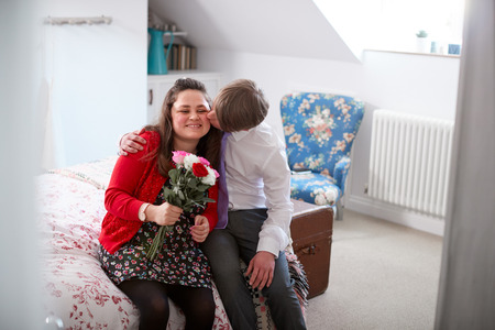 Loving Young Downs Syndrome Couple Sitting On Bed With Man Giving Woman Flowers Stock Photo