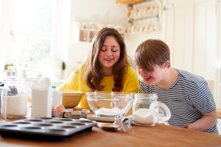 Young Downs Syndrome Couple Baking In Kitchen At Home