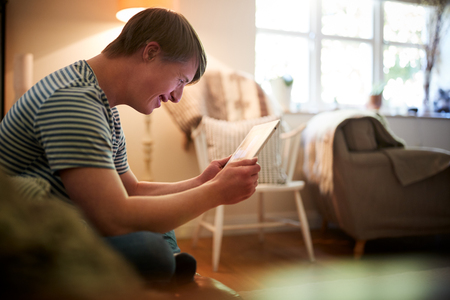 Young Downs Syndrome Man Sitting On Sofa Using Digital Tablet At Home Stock Photo