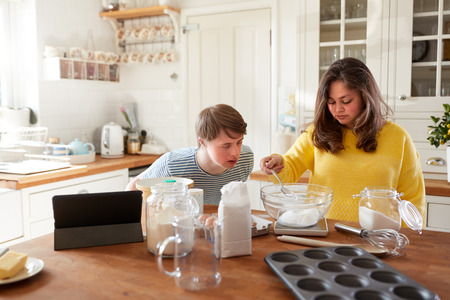 Young Downs Syndrome Couple Following Recipe On Digital Tablet To Bake Cake In Kitchen At Home Stockfoto